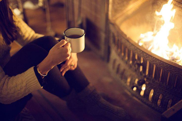 a person sitting in front of a fireplace holding a mug of tea