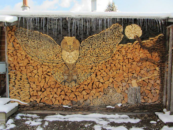 a wood pile, stacked in such a way that it looks like an owl in flight
