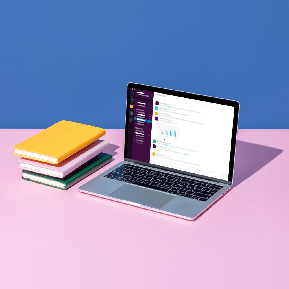a stack of books next to a laptop with a stylized version of Slack visible on it